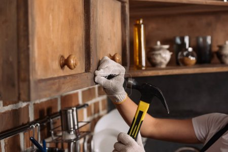cropped shot of repairwoman in work gloves hammering nail into kitchen cabinet