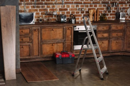 interior of loft style kitchen with stepladder, toolbox and laminate planks on floor