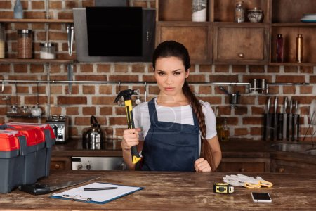 serious young repairwoman with hammer standing at kitchen and looking at camera