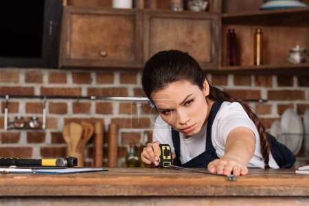 confident young repairwoman measuring kitchen table with tape