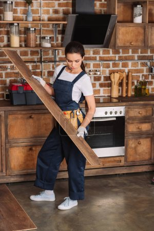 attractive young repairwoman installing laminate onto kitchen floor