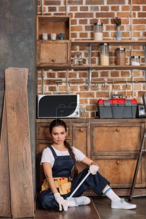 attractive young repairwoman relaxing while sitting on floor at kitchen