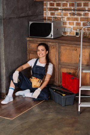 happy young repairwoman relaxing while sitting on floor at kitchen