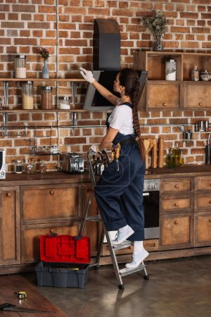beautiful young repairwoman standing on stepladder at kitchen