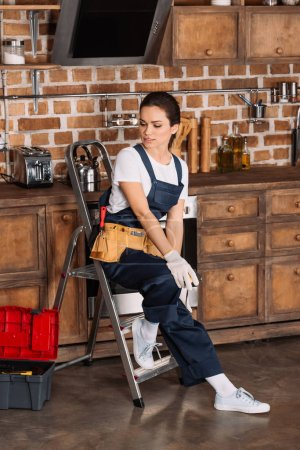 beautiful young repairwoman sitting on stepladder at kitchen
