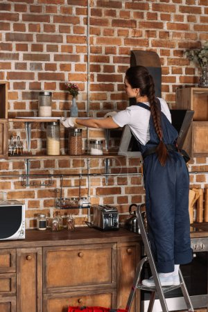 young repairwoman in overall measuring shelf at kitchen