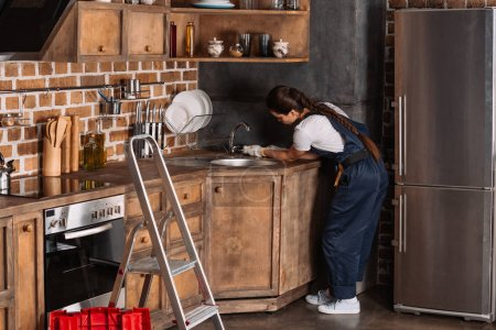 young female plumber with wrench repairing kitchen sink