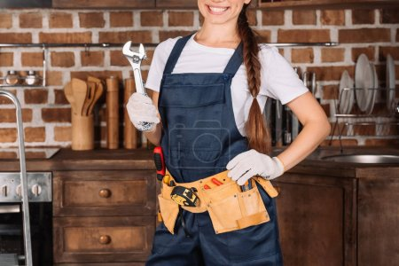 cropped shot of smiling young repairwoman with toolbelt and wrench
