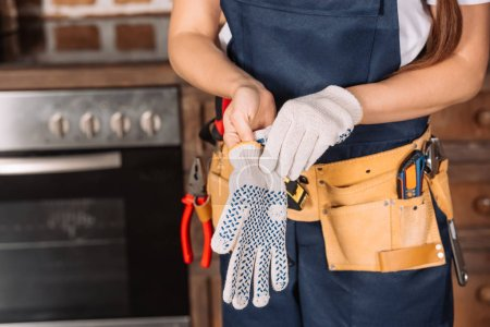 cropped shot of repairwoman putting on work gloves at kitchen