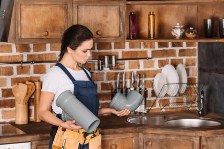 attractive young female plumber in overall with plastic pipes at kitchen