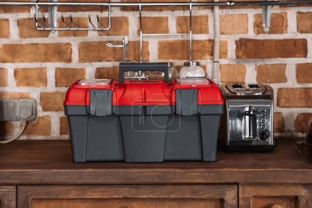 close-up shot of toolbox standing on kitchen table with toaster in front of brick wall