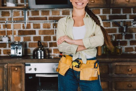 cropped shot of smiling repairwoman with crossed arms standing in front of kitchen table with oven