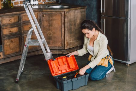 beautiful young repairwoman with toolbox sitting on floor of kitchen