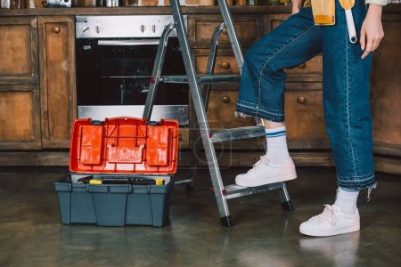 cropped shot of repairwoman in jeans standing on stepladder at kitchen