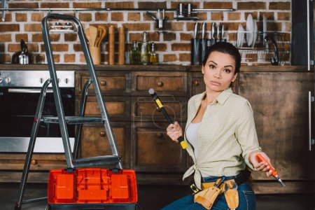 confused young repairwoman with hammer and pliers sitting on floor of kitchen