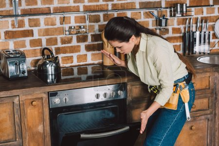 confused young repairwoman looking at broken oven with smoke inside
