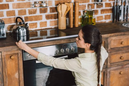 Photo for Serious young repairwoman measuring width of oven at kitchen - Royalty Free Image