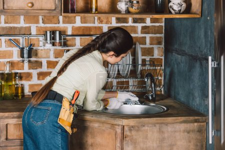 young repairwoman with wrench fixing kitchen sink