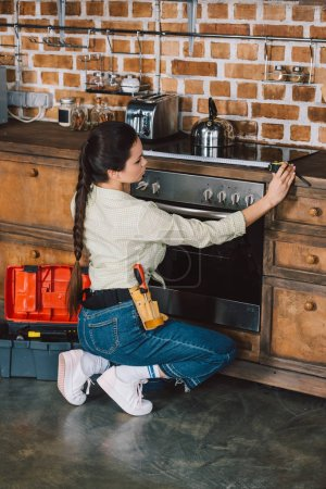 attractive young repairwoman measuring width of oven at kitchen