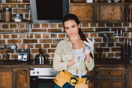 attractive young repairwoman in work gloves standing at kitchen and looking at camera