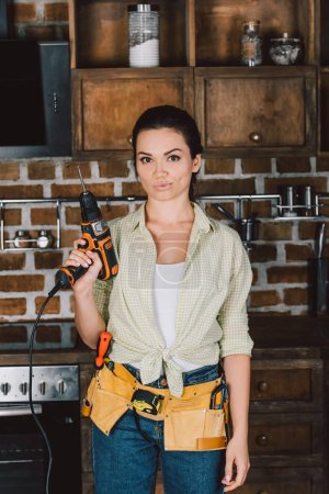 attractive young repairwoman holding power drill and looking at camera
