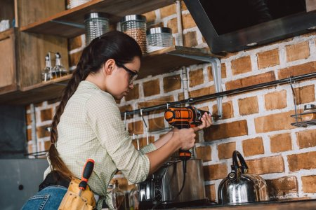 attractive young repairwoman in protective eyeglasses drilling wall at kitchen