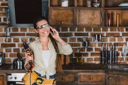 happy young repairwoman in protective glasses with power drill talking by phone