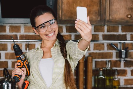 happy young repairwoman in protective glasses with power drill taking selfie