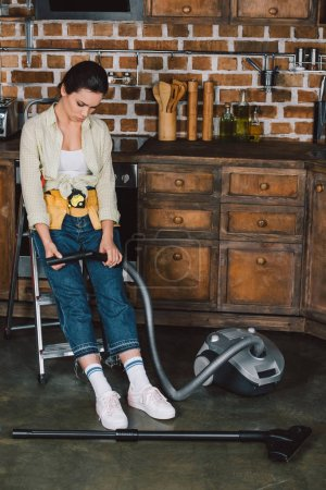 sad young repairwoman looking at broken vacuum cleaner while sitting on stepladder at kitchen