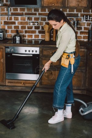 attractive young woman with toolbelt using vacuum cleaner at kitchen