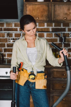 confused young repairwoman looking at vacuum cleaner at kitchen