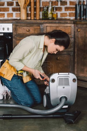 attractive young repairwoman fixing vacuum cleaner with screwdriver