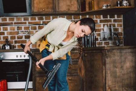 confused young woman with toolbelt looking at vacuum cleaner pipe at kitchen