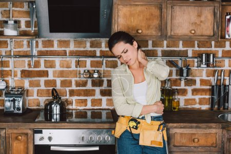 tired young repairwoman with pain in neck leaning back on kitchen table