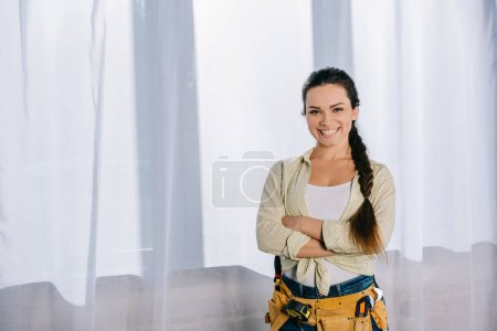 beautiful young repairwoman with toolbelt and crossed arms looking at camera