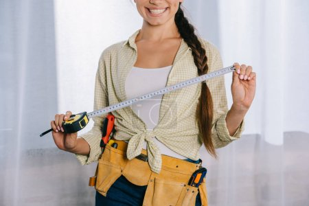 cropped shot of smiling young repairwoman with measuring tape