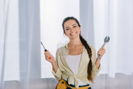 happy young repairwoman with wrench and screwdriver looking at camera