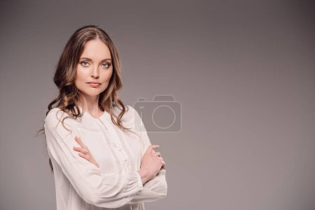 beautiful woman standing with crossed arms isolated on grey background