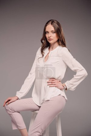 serious beautiful woman posing on chair isolated on grey background