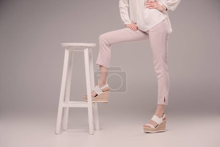 cropped image of female model standing with leg on chair on grey background