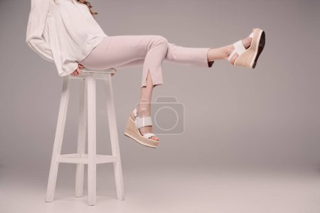 cropped image of woman posing and showing legs on chair on grey background