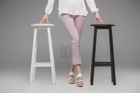 Photo pour Image recadrée du modèle féminin debout entre les chaises sur fond gris - image libre de droit