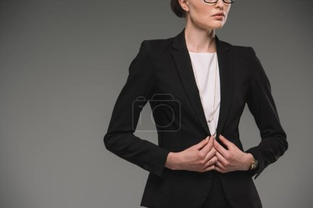 cropped image of serious businesswoman isolated on grey background