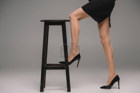 cropped image of businesswoman in shoes with high heels standing with leg on chair on grey background