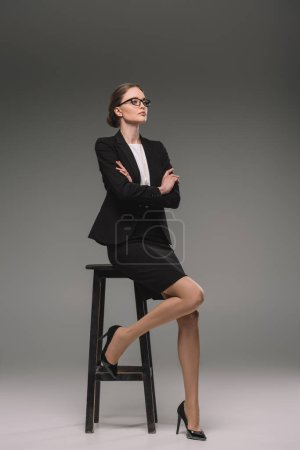 beautiful businesswoman in eyeglasses sitting on chair with crossed arms on grey background
