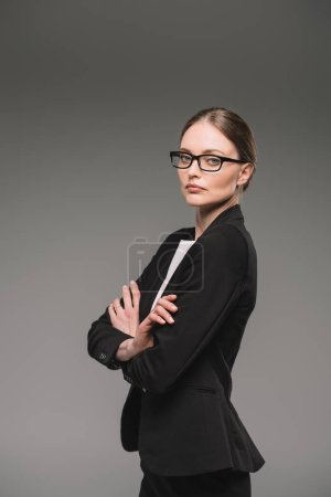 Photo for Confident businesswoman in eyeglasses standing with crossed arms isolated on grey background - Royalty Free Image