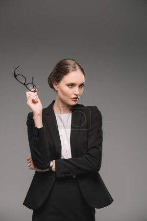beautiful businesswoman holding eyeglasses and looking away isolated on grey background