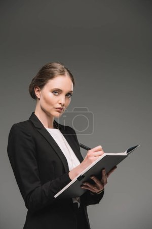 Photo for Attractive businesswoman writing in textbook isolated on grey background - Royalty Free Image