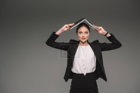 smiling businesswoman holding textbook over head isolated on grey background