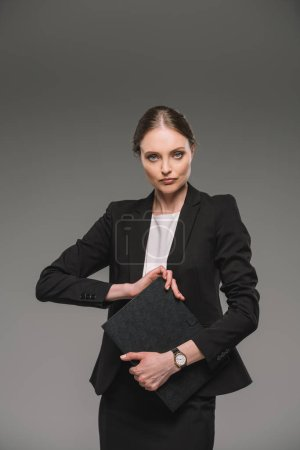 serious businesswoman holding textbook isolated on grey background